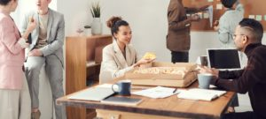 Office workers sharing food and eating at the desk