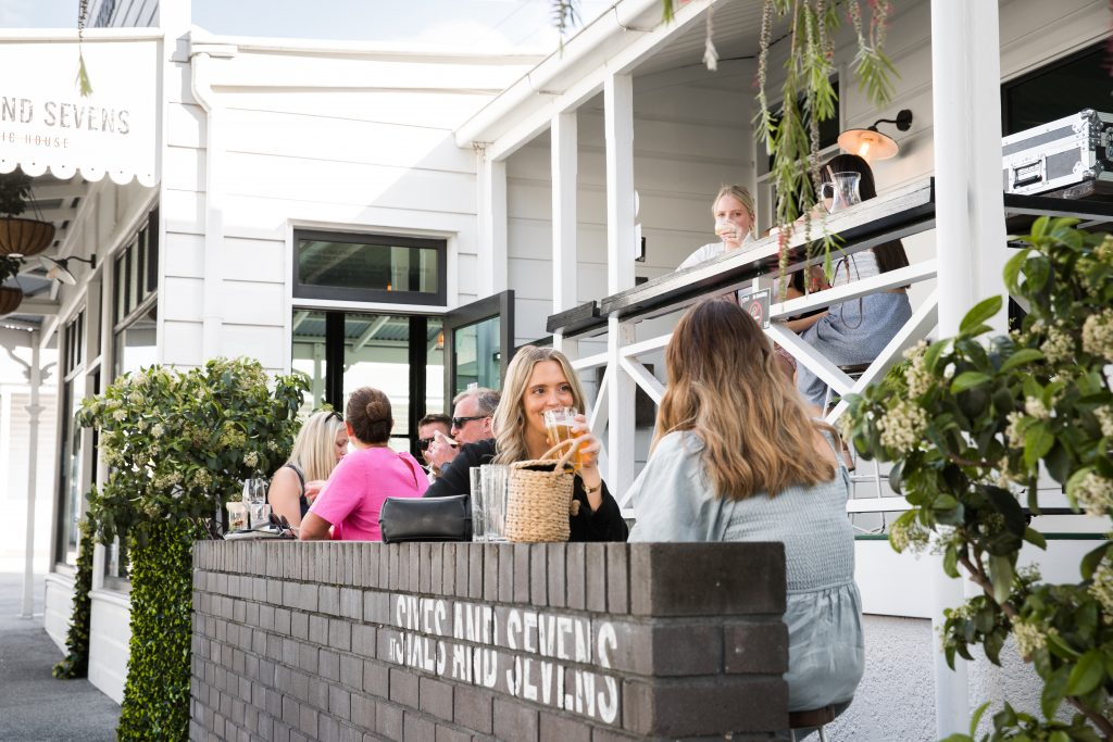People sitting and drinking outside at a hospitality venue with plants and greenery around