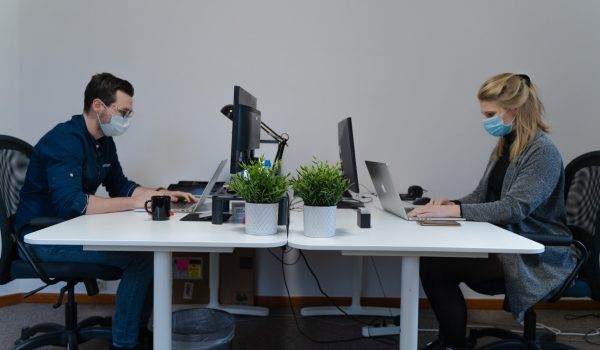 An office setting during COVID-19 with two office workers sat at desks working with face masks on